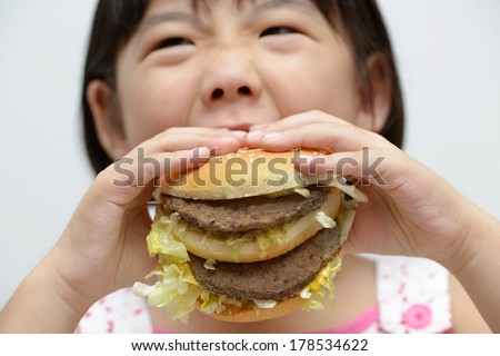 Little girl with big burger or sandwich inside mouth - stock photo