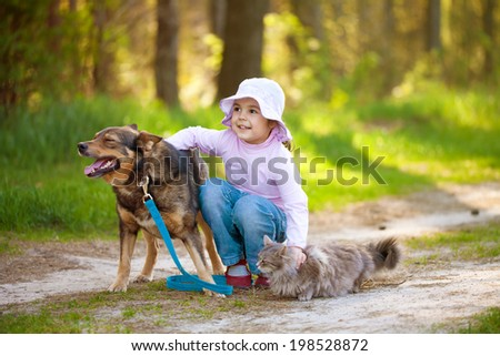 Little girl with big dog and cat in the forest - stock photo