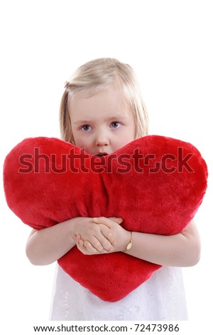 little girl with big red heart shaped pillow in her arms. isolated on white