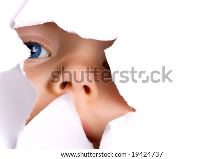 Little girl with blue eyes peeking through torn paper hole - stock photo