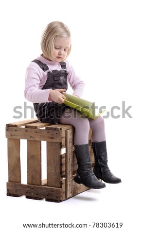 little girl with book seated on a wooden crate. Isolated on white background