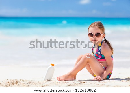 Little girl with bottle of sun cream sitting at tropical beach - stock photo