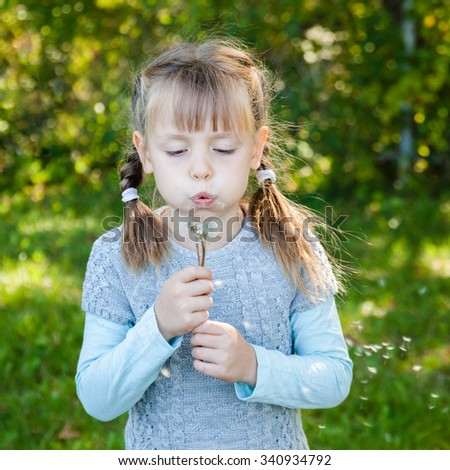 Little girl with braids in tunic and sweater blowing on white dandelion.