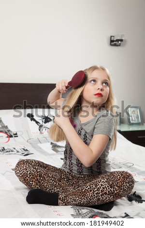 Little girl with bright make up combs hair sitting on bed