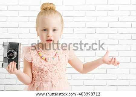 little girl with camera made helpless gesture, looking at camera