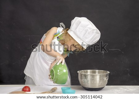 little girl with chef hat,making cup cakes - stock photo