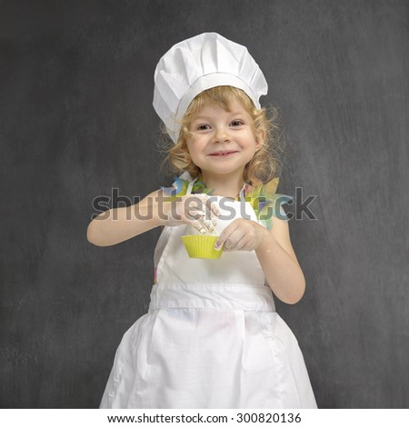 little girl with chef hat, making cupcakes - stock photo