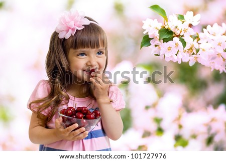 little girl with cherry berries bowl in garden - stock photo