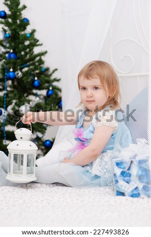 Little girl with christmas gifts at fir tree - stock photo