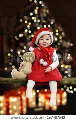 little girl with christmas hat and teddy bear in front of a christmas tree - stock photo