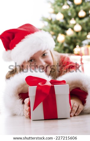 Little girl with christmas, red gift - stock photo