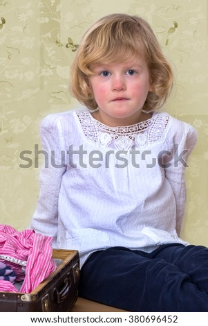 Little girl with clothes suitcase