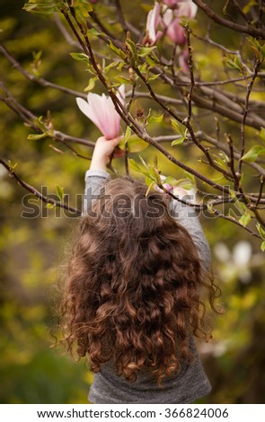 Little girl with curly hair playing in the garden