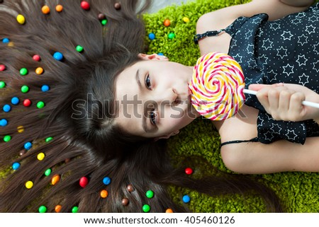 Little girl with dark hair lying on the floor among the sweets. Top view of a big yellow and pink lollipops in my mouth. Many candies in her hair. fun and excitement on the face of the child. - stock photo