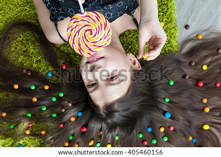 Little girl with dark hair lying on the floor among the sweets. Top view of a big yellow and pink lollipops in hands. Many candies in her hair. fun and excitement on the face of the child. - stock photo