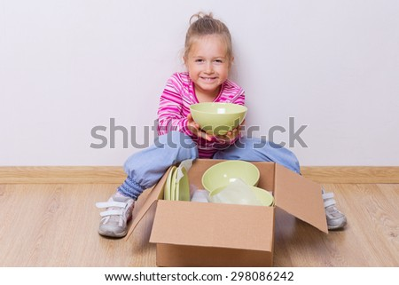 Little girl with dishware on the floor - stock photo