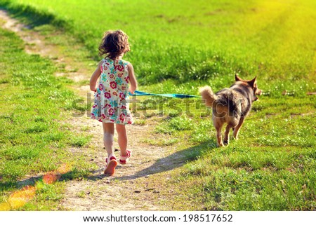 Little girl with dog running outdoor - stock photo