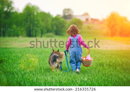 Little girl with dog walking on the field to the picnic - stock photo