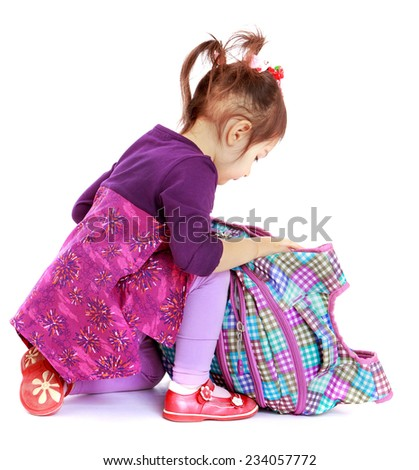 little girl with enthusiasm unzips backpack in search of a gift.Isolated on white background. - stock photo