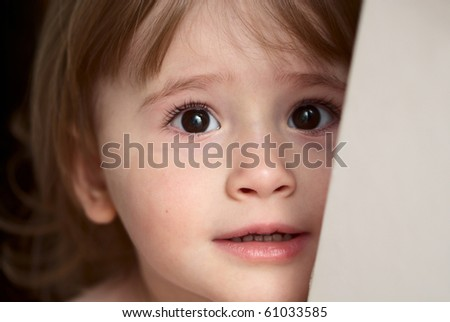Little girl with eyes full of scare and sadness - stock photo