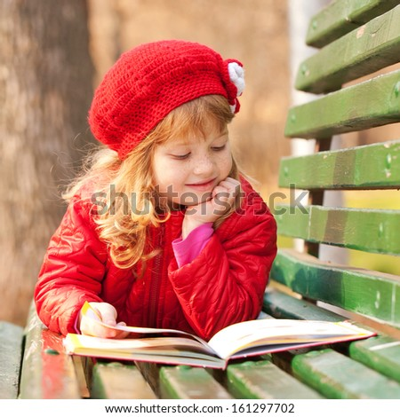 Little girl with freckles wearing a red reading a book on a bench in the park. - stock photo