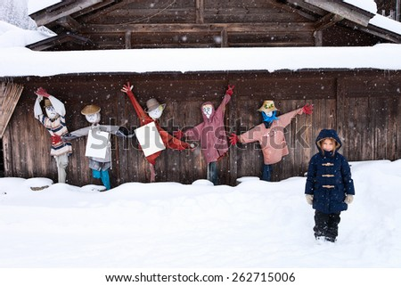 Little girl with funny scarecrows at historic Japanese village Shirakawa-go at winter, one of Japan's UNESCO world heritage sites - stock photo