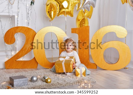 Little girl with gift sitting on the floor. The celebration of the New Year 2016. Toys and balloons. Holiday and fun. - stock photo
