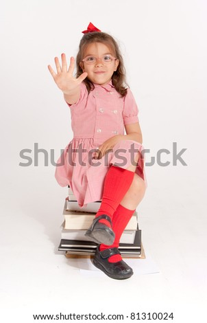 Little girl with glasses and an stopping gesture sitting on a pile of books - stock photo