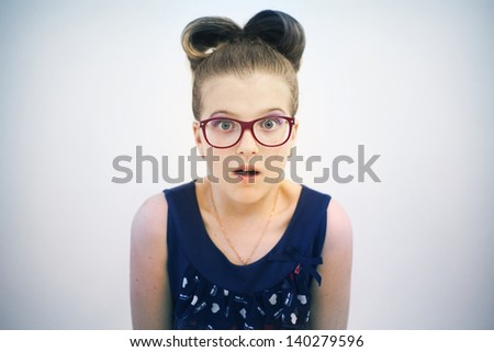 little girl with glasses and hairstyle close up looking surprised - stock photo