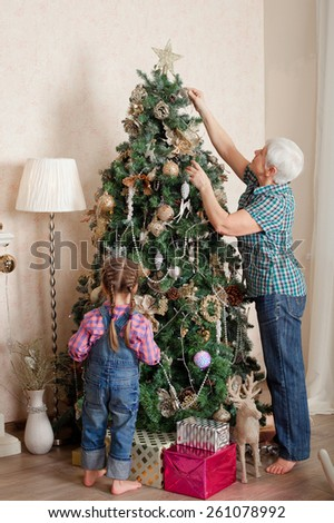 Little girl with grandmother decorating christmas tree at home.  - stock photo