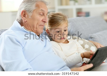 Little girl with grandpa playing with digital tablet