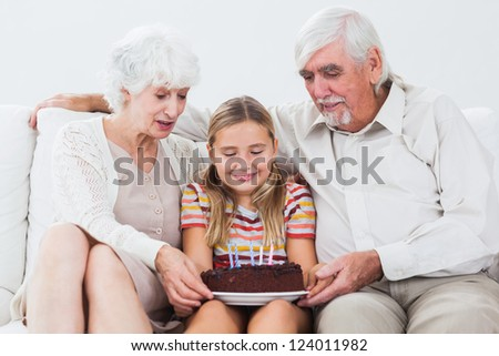 Little girl with grandparents celebrating birthday with cake on the couch