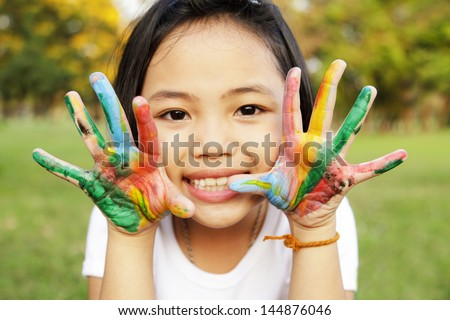 Little girl with hands painted in colorful paint - stock photo
