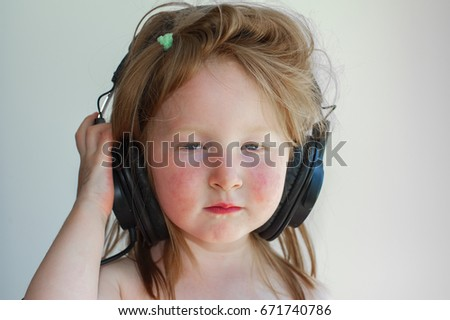Little girl with headphones is serious about music