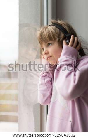 Little girl with headphones listening to the music and looking through window - stock photo