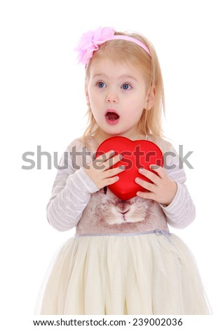 Little girl with heart in hands. Studio photo, isolated on white background.