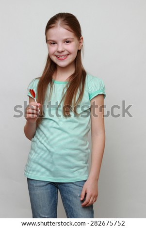 Little girl with heart symbol lolly pop - stock photo