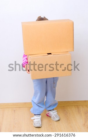 Little girl with heavy boxes