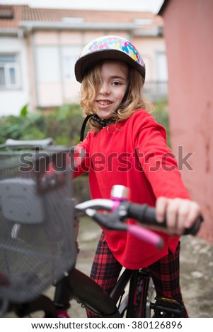 Little girl with her bicycle outdoors. She is looking at camera and smiling.