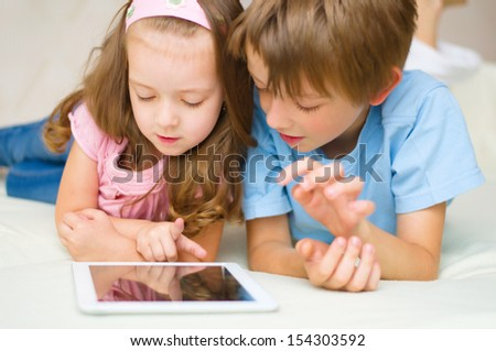little girl with her brother using tablet computer