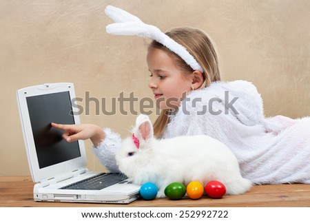 Little girl with her bunny using computer together preparing for easter-shallow depth of field - stock photo