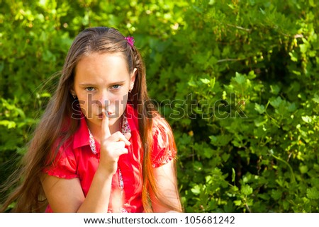 Little girl with her finger over her mouth, hushing. - stock photo
