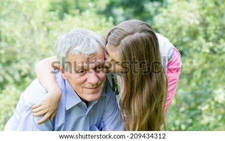 Little girl with her grandfather - stock photo