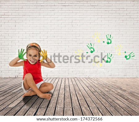 little girl with her hands painted on a room with white bricks wall and wood floor