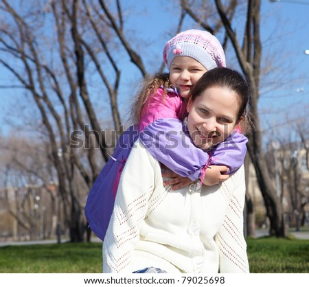 little girl with her mother in spring park