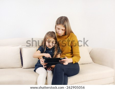 little girl with her mother using tablet device on the sofa at home, happy family, technology concept - stock photo
