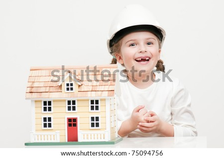 Little girl with house model (self made house) - stock photo