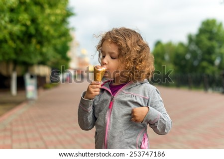 Little girl with icecream in the park - stock photo