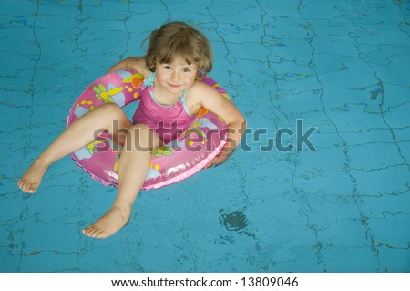 Little girl with inner tube floating on swimming pool - stock photo