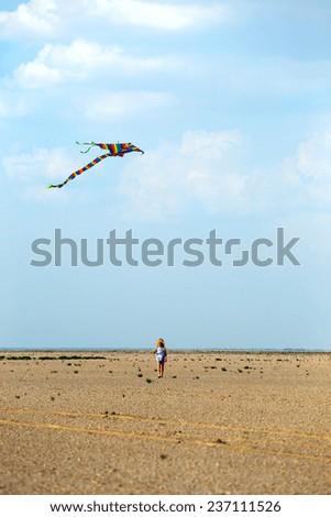 little girl with kite at the summer desert landscape  - stock photo